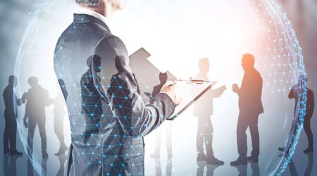 Rear view of businessman with clipboard with his teammates silhouettes and double exposure of planet hologram. Concept of international company and trade. Toned image Stock Photo