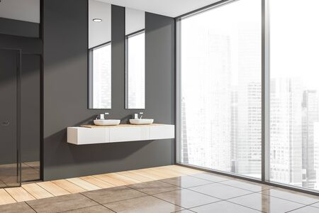 Corner of panoramic bathroom with dark gray walls, wooden and tiled floor, two sinks standing on white countertop with vertical mirrors above it and shower stall with glass door. 3d rendering Banco de Imagens