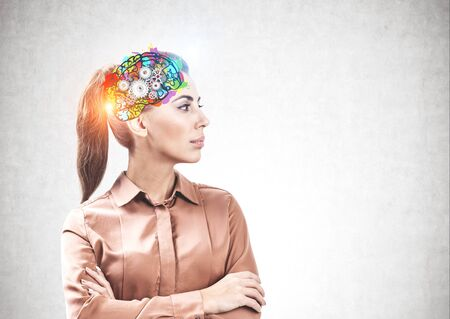 Portrait of confident businesswoman standing with crossed arms near concrete wall with colorful brain sketch. Concept of brainstorming and creative thinking. Mock up
