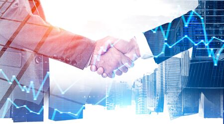 Two young businessmen shaking hands over city background with double exposure of graphs. Stock market and partnership concept. Toned image blurred 写真素材