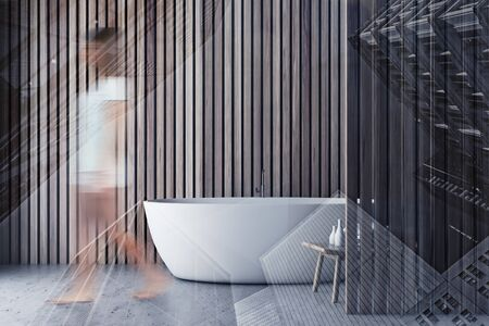 Young woman walking in minimalistic bathroom interior with wooden walls, concrete floor and comfortable white bathtub. Toned image double exposure blurred