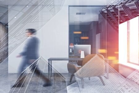 Businessman walking in CEO office with white walls, concrete floor, gray computer desk and armchair for visitors. Toned image double exposure blurred Фото со стока