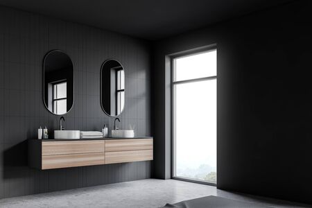Corner of modern bathroom with gray tile and gray walls, concrete floor, double sink standing on wooden countertop with towels and two oblong mirrors and loft window. 3d rendering