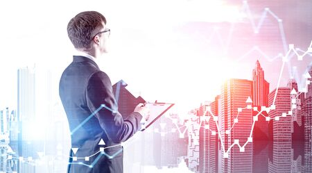 Side view of young businessman in glasses with clipboard over cityscape background with double exposure of forex charts. Concept of stock market and analysis. Toned image Stock Photo