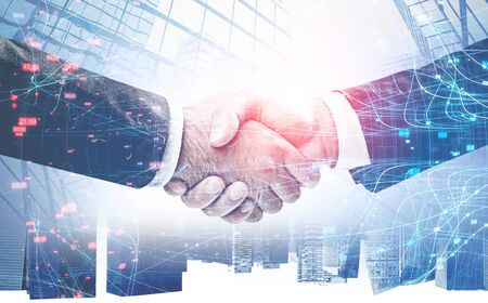 Close up of two businessmen shaking hands over abstract city background with double exposure of network interface. Concept of partnership and hi tech. Toned image 写真素材