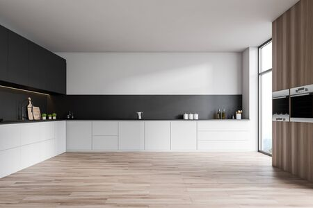 Interior of stylish kitchen with white and black walls, wooden floor, white countertops, gray cupboards and two ovens. 3d rendering