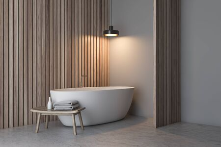 Corner of minimalistic bathroom with white and wooden walls, concrete floor, white bathtub and chair with towels and shampoos. 3d rendering