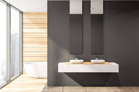 Interior of stylish bathroom with dark gray and wooden walls, wooden and tiled floor, two sinks standing on white countertop with vertical mirrors above it and and bathtub in background. 3d rendering