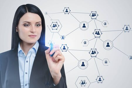 Serious beautiful businesswoman with dark hair working with social network interface. Concept of social media and recruitment in business.