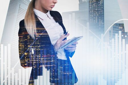 Serious blonde businesswoman making notes in city with double exposure of diagrams. Stock market and analysis concept. Toned image Stock Photo