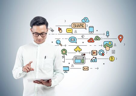 Smiling Asian man in glasses with tablet computer standing near gray wall with colorful social media sketch drawn on it. Concept of using social media for business promotion