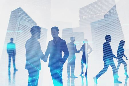 Silhouettes of business people shaking hands and working together over skyscraper background with double exposure of network hologram. Concept of hi tech and teamwork. Toned image blurred Imagens