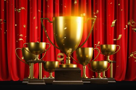 Gold champion trophies on dark wooden stands with confetti standing on black surface over red curtain background. Concept of leadership in business and sport. 3d rendering toned image Reklamní fotografie
