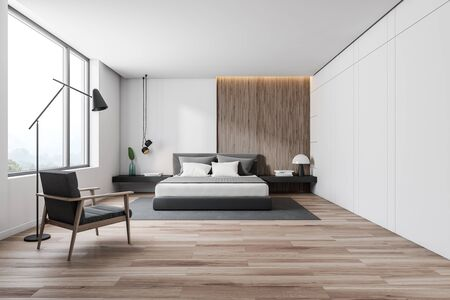 Interior of minimalistic bedroom with white and wooden walls, wooden floor, gray master bed with black bedside tables and gray carpet. Comfortable armchair with floor lamp. 3d rendering Stock Photo
