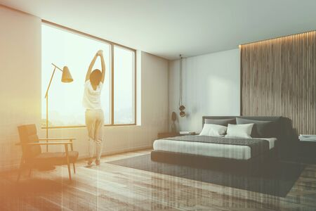 Rear view of woman in pajamas standing in stylish bedroom corner with white and wooden walls, wooden floor and master bed on gray carpet. Comfortable armchair. Toned image double exposure Stok Fotoğraf