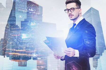 Serious young businessman in glasses reading documents over cityscape background with double exposure of social network interface. Concept of HR. Toned image