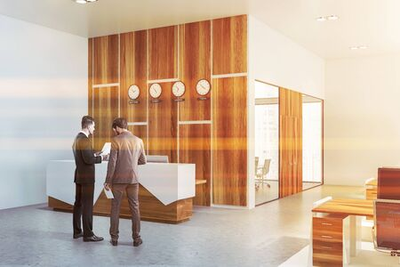 Two businessmen discussing documents in office hall near white and wooden reception desk with clocks showing world time. Concept of stock market company. Toned image
