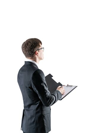 Side view of serious young businessman with fair hair wearing dark suit and glasses and holding clipboard. Concept of contract signing. Isolated portrait.