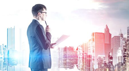 Serious young businessman in suit and glasses holding document and thinking looking at cityscape. Concept of business planning. Toned image double exposure Фото со стока