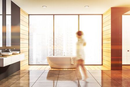 Woman walking in panoramic bathroom with gray and wooden walls, tiled floor, double sink standing on white countertop and white bathtub. Toned image blurred Reklamní fotografie - 124813747