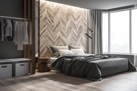 Corner of modern bedroom with gray and wooden walls, wooden floor, master bed with round bedside table and wardrobe with clothes and boxes. 3d rendering Stock Photo