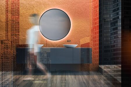 Young woman walking in modern bathroom interior with orange walls, wooden floor and double sink standing on gray countertop. Toned image double exposure blurred