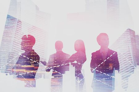 Team of young and confident business people standing together over night cityscape background with double exposure of charts. Concept of teamwork and stock market. Toned image