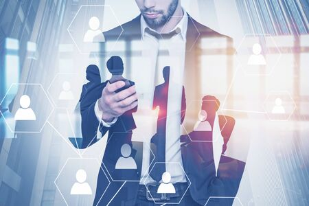 Portrait of businessman with smartphone with double exposure of business people in office and social network icons. Concept of social connection in business and HR. Toned image 3d rendering Stock Photo