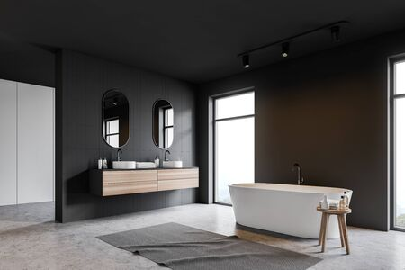 Corner of loft bathroom with gray and gray tile walls, concrete floor, white bathtub standing near window and double sink with two mirrors above it. 3d rendering