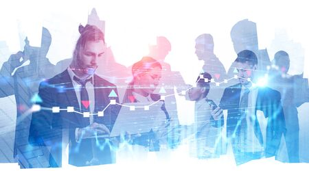 Diverse business team working with gadgets over abstract city background with double exposure of forex charts. Concept of teamwork and trading. Toned image blurred
