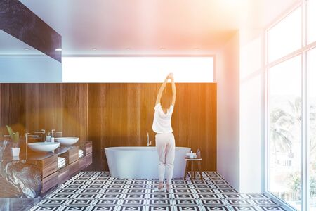Rear view of young woman standing in panoramic bathroom interior with black marble and wooden walls, tiled floor, double sink and white bathtub. Toned image