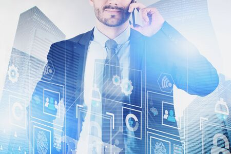 Smiling businessman talking on smartphone in city with double exposure of digital business interface. Concept of hi tech and smart city. Toned image Stock Photo