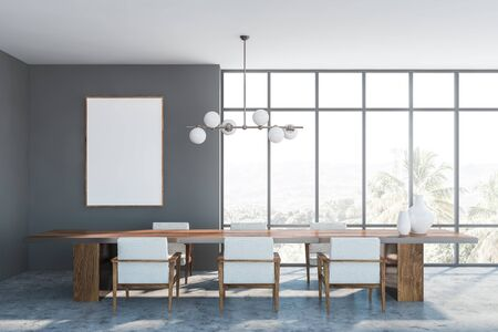 Interior of panoramic dining room with gray walls, concrete floor, dark wooden table with armchairs and stylish lamp. Mock up poster on the left. 3d rendering 版權商用圖片