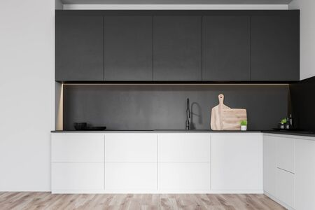 Interior of minimalistic kitchen with white and gray walls, wooden floor, white countertops with built in sink and black cupboards with dishes and cutting boards. 3d rendering