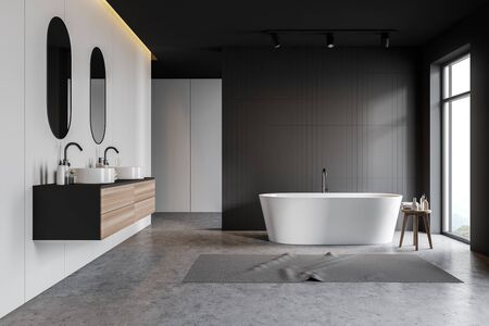 Interior of stylish bathroom with gray tile and white walls, concrete floor, white bathtub with carpet near window and double sink with mirrors on wooden countertop. 3d rendering