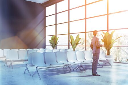 Young businessman with coffee standing in modern airport waiting room with gray walls, panoramic windows and rows of white chairs. Toned image