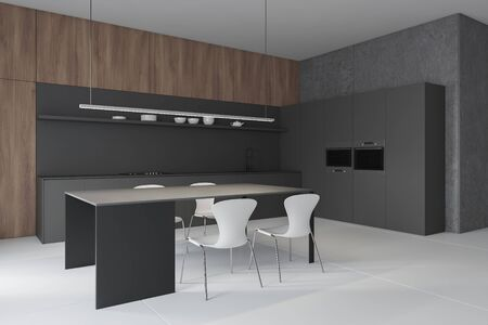 Corner of stylish kitchen with concrete and wooden walls, gray countertops with sink and cooker, gray cupboard with two ovens and table with white chairs. 3d rendering Stock Photo