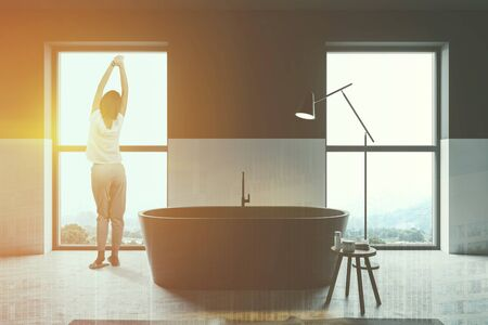 Rear view of woman in pajamas standing in white and black bathroom interior with concrete floor, black bathtub and rug on the floor. Toned image double exposure Reklamní fotografie - 124819437