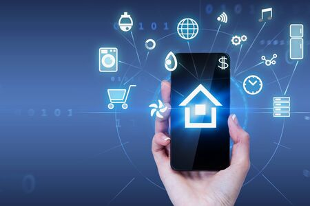 Woman hand holding smartphone with glowing smart home interface icons and HUD interface over dark blue background. Toned image double exposure Фото со стока