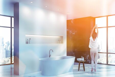 Rear view of woman in pajamas standing in modern bathroom corner with white and black marble walls, white marble floor and white bathtub. Toned image Reklamní fotografie - 124819441