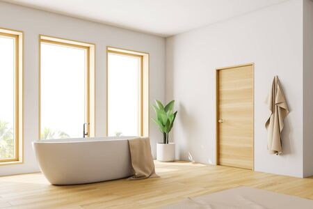 Corner of loft bathroom with white walls, wooden floor and white bathtub with towel on it standing under three windows. Door in the wall. 3d rendering