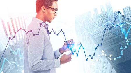 Side view of young African American businessman in glasses making notes over cityscape background. Double exposure of charts. Stock market and analysis concept. Toned image