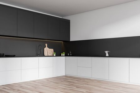 Corner of minimalistic kitchen with white and gray walls, wooden floor, white countertops with built in sink and black cupboards with dishes and cutting boards. 3d rendering Standard-Bild - 124974557