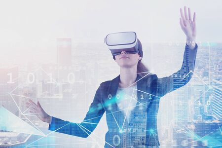 Young businesswoman in VR glasses working with network interface over cityscape background. Concept of hi tech and business. Toned image double exposure Imagens
