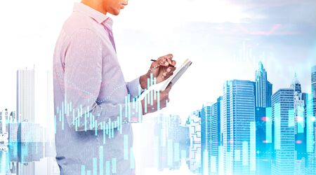 Side view of young African American businessman making notes over cityscape background. Double exposure of charts. Stock market and business education concept. Toned image