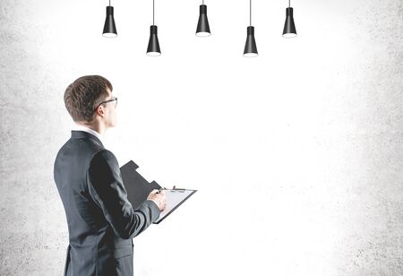 Side view of serious young businessman with fair hair wearing dark suit and glasses and holding clipboard near concrete wall with lamps. Mock up