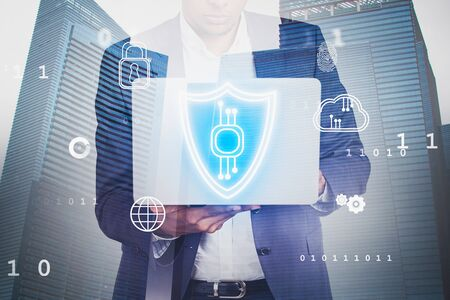 Serious African American businessman using laptop with double exposure of cyber security interface in city. Concept of data protection. Stock Photo