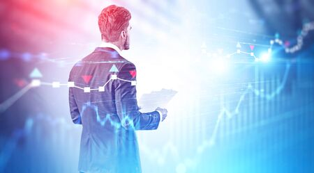 Rear view of young caucasian businessman holding documents over blurred blue background with double exposure of forex charts. Concept of trading. Toned image Stock Photo