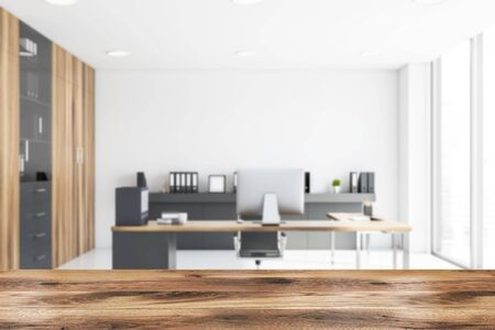 Blurred interior of CEO office with white walls, tiled floor, gray and wooden computer desk, shelf with folders and bookcase. Table for your product in foreground. 3d rendering Banco de Imagens