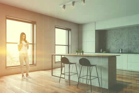 Young woman with smartphone and coffee standing in stylish kitchen with white and concrete walls, white countertops and bar with stools. Toned image double exposure